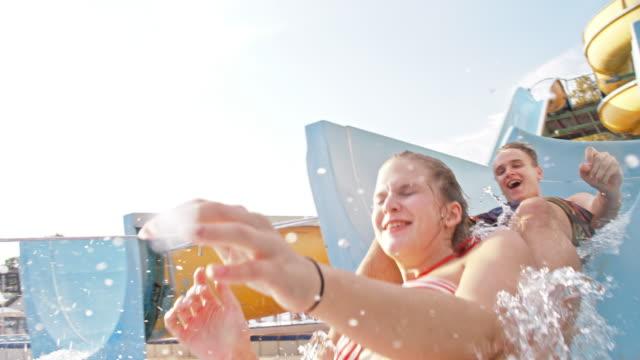 stockvideo's en b-roll-footage met slo mo paar genieten van een ritje op de glijbaan - waterpark