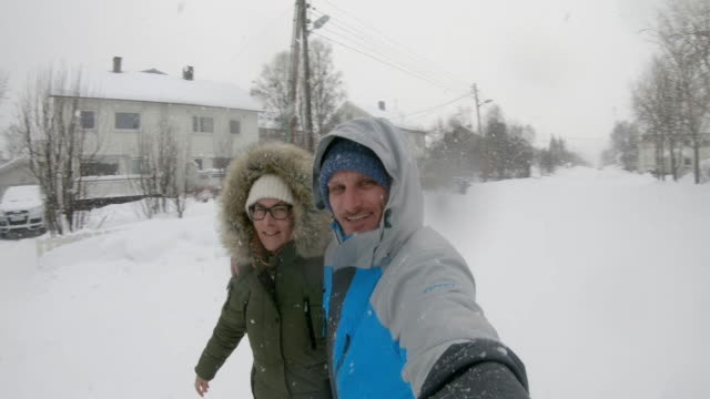 slo mo couple enjoying a snowy winter day - mid adult couple stock videos & royalty-free footage