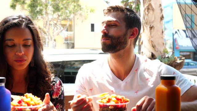 ms couple enjoying acai bowls while sitting at juice bar - cibo biologico video stock e b–roll