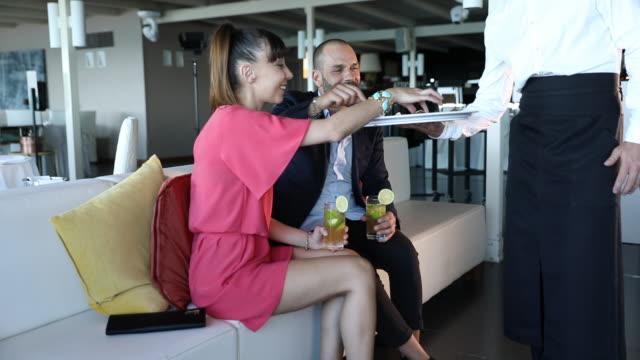 paar genießt einen aperitif, bevor es in einem luxusrestaurant isst - paar mittleren alters stock-videos und b-roll-filmmaterial