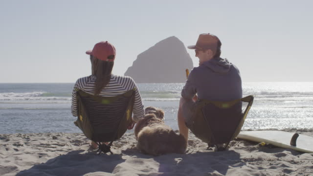 couple enjoying beers on the beach - oregon coast stock videos & royalty-free footage