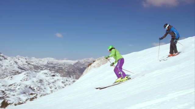 pan couple enjoying carving on the sunny ski slope - winter sport stock videos and b-roll footage