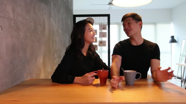 couple enjoying coffee at dinning table in the morning bonding time talking to each other - tan stock videos and b-roll footage