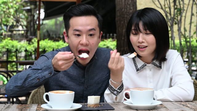 couple enjoying coffee with woman trying cheesecake - taipei stock videos & royalty-free footage