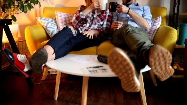 Paar genieten kopje thee na het beëindigen van hun nieuwe meubels monteren