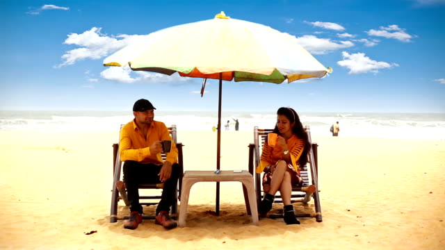 couple enjoying hot coffee on tropical sandy beach, goa - indian couple tea stock videos & royalty-free footage