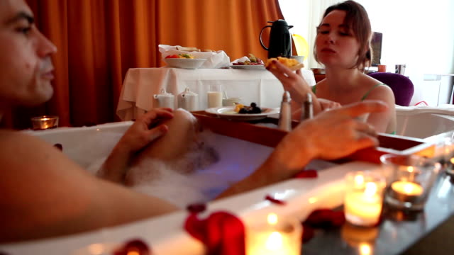 Couple enjoying Jacuzzi and buffet in hotel room