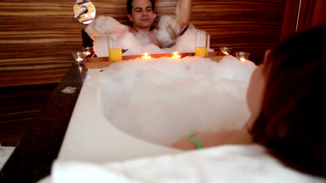 Couple enjoying hot tub and buffet in hotel room