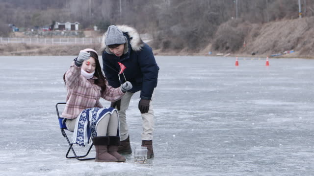 couple enjoying ice smelt fishing in winter / hongcheon, south korea - fishing rod stock videos & royalty-free footage