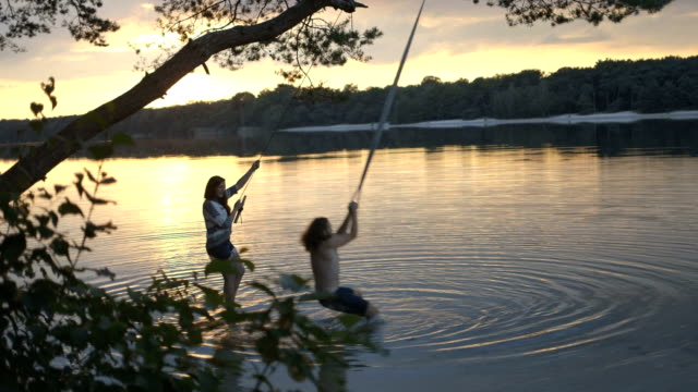 Couple enjoying rope swing over river