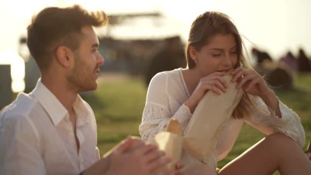couple enjoying sandwiches on picnic - panino ripieno video stock e b–roll