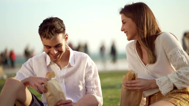 ピクニックでサンドイッチを楽しむカップル - 食べ物 サンドイッチ点の映像素材/bロール