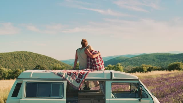vídeos de stock e filmes b-roll de couple enjoying scenery while sitting on van roof - acampar