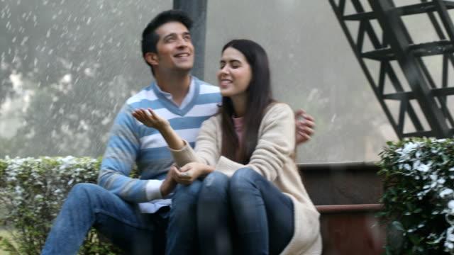 ms pan couple enjoying snowfall in park / india - braccio attorno alle spalle video stock e b–roll