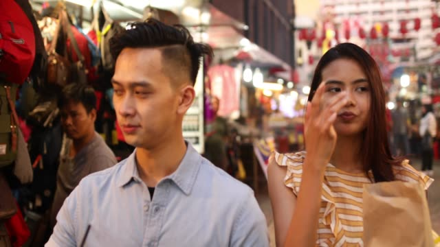Couple enjoying street food at the Jalan Petaling market