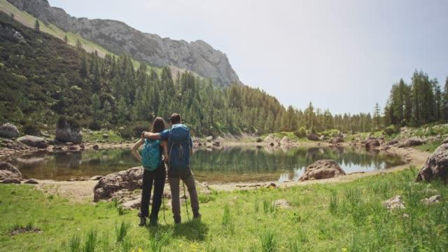 vidéos et rushes de couple de profiter de la beauté du lac de montagne et de ses environs par une journée ensoleillée - zoom avant
