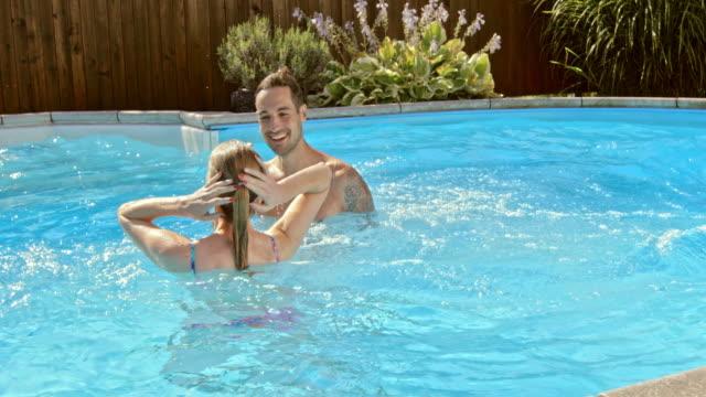 vidéos et rushes de au ralenti couple de ds profitant de la piscine sur la journée ensoleillée - clôture jardin