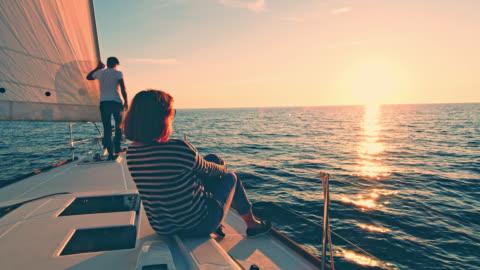 ws couple enjoying the sailing at sunset - sailing boat stock videos & royalty-free footage