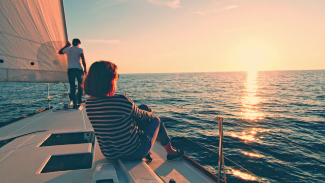 ws couple enjoying the sailing at sunset - nautical vessel stock videos & royalty-free footage