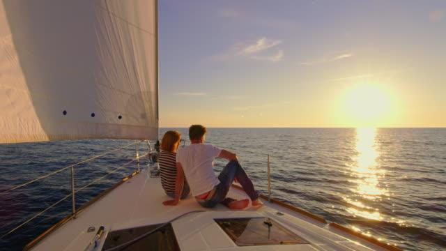 slo mo couple enjoying the view of a sunset on a boat - barca da diporto video stock e b–roll