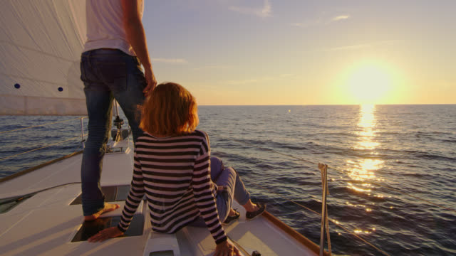slo mo couple enjoying the view of a sunset on a boat - human relationship stock videos and b-roll footage