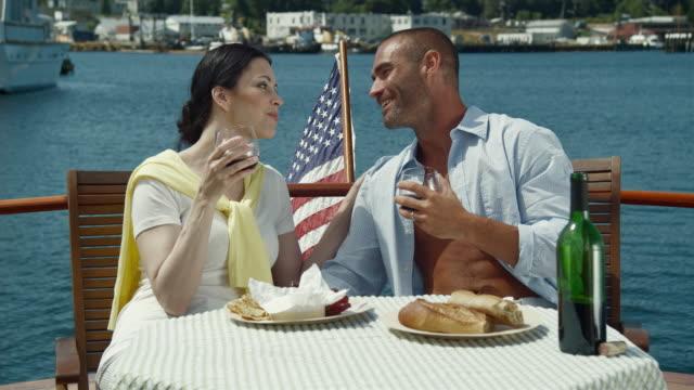 MS Couple enjoying wine and cheese on boat / Seattle, Washington, USA
