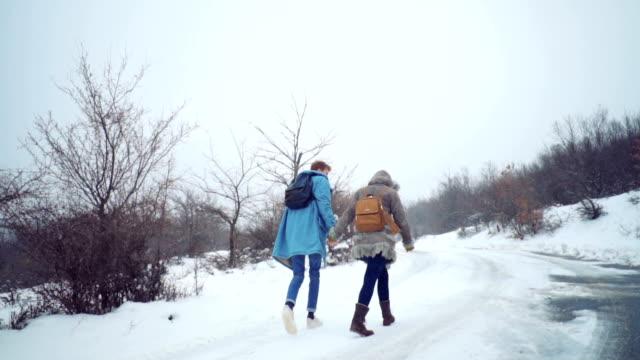 冬を楽しんでいるカップルを歩く - 人の背中点の映像素材/bロール