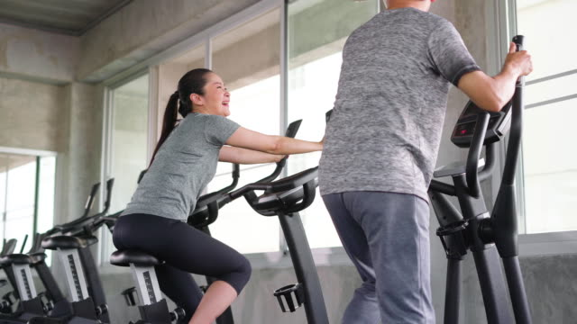 couple enjoying workout on exercise machine - cross trainer stock videos and b-roll footage