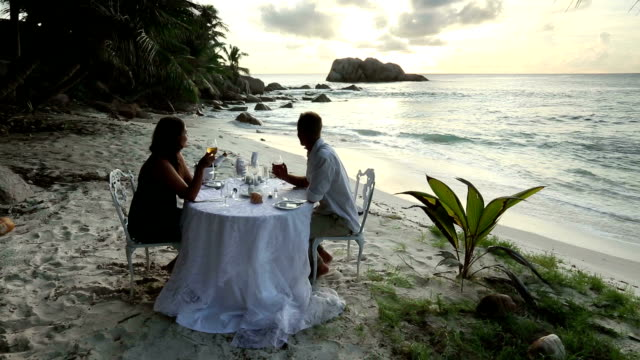 A couple enjoys a romantic dinner on a secluded beach in Seychelles.