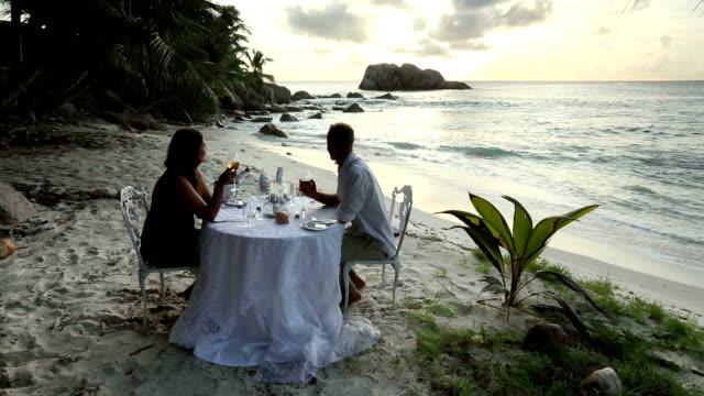 A couple enjoys a romantic dinner on a secluded beach in Seychelles.