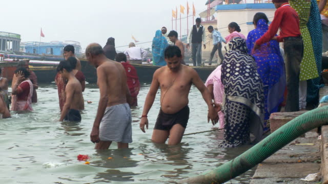 Couple enter Ganges River other pilgrims, bathers, around them