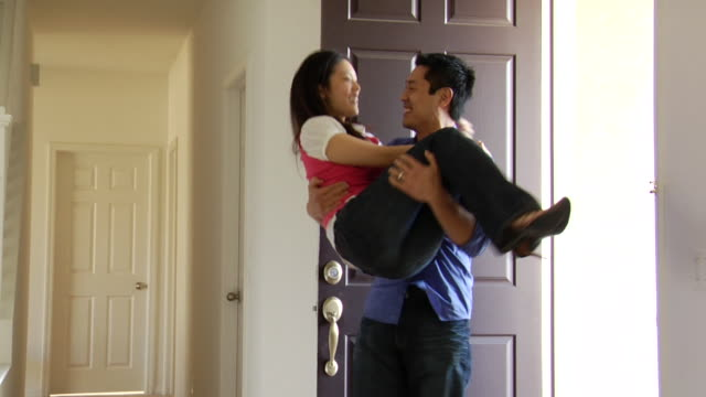 MS Couple entering new home, then man lifts and carries woman inside / Los Angeles, California, USA
