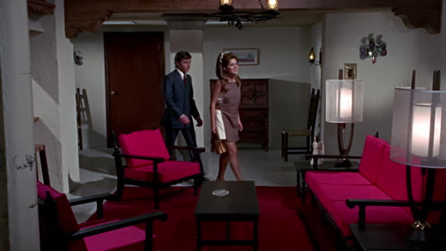 couple enters a 1970 house with red chairs and retro style. - living room stock videos & royalty-free footage