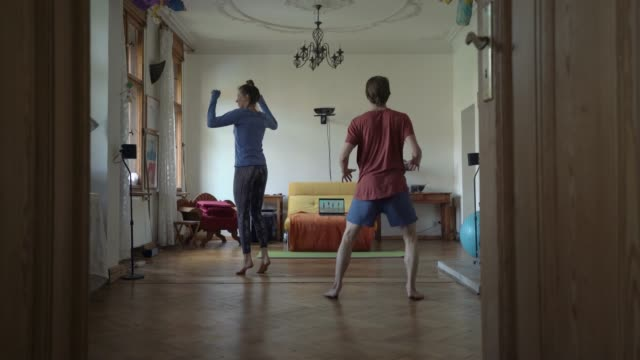 stockvideo's en b-roll-footage met couple exercising together in living room - mid volwassen koppel