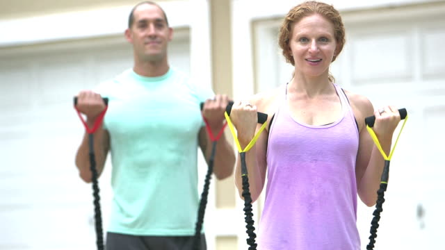 Couple exercising together with resistance bands