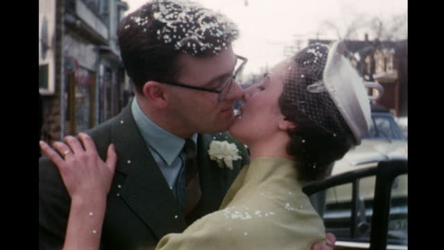stockvideo's en b-roll-footage met 1955 montage couple exiting church, rice is thrown, couple kissing, groom carrying bride / toronto, canada - 1955