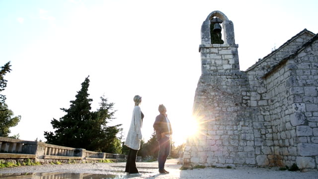 Couple explore ancient chapel on Mediterranean hillside