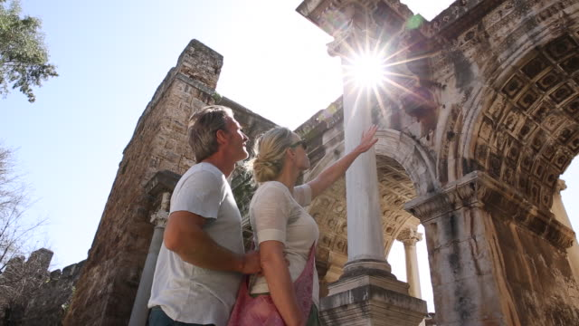 couple explore ancient hadrian's gate, roman ruins - old ruin stock videos and b-roll footage