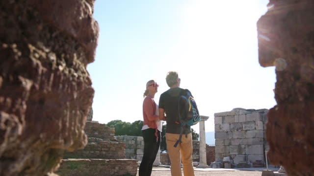 couple explore monument ruins, with info sheet - izmir stock videos & royalty-free footage