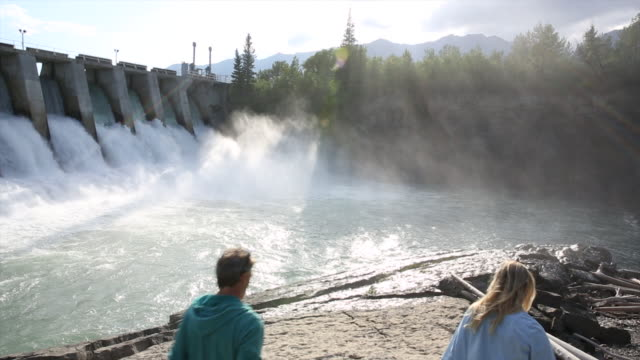 vídeos de stock e filmes b-roll de couple explore near hydroelectric dam - barragem estrutura feita pelo homem