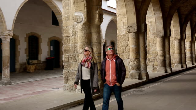 Couple explore portico of ancient cathedral
