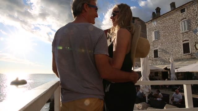 couple explore ramparts of ancient town, look out to sea - arm around stock videos & royalty-free footage