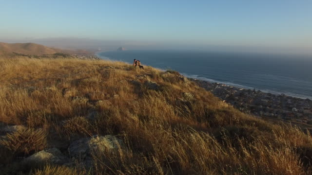 A couple explores the hilltops of Cayucos and the stunning views over Morrow Bay and Morrow Rock