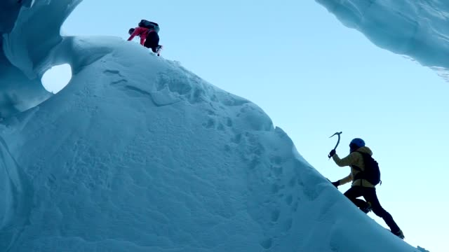 couple exploring ice cave - climbing stock videos & royalty-free footage