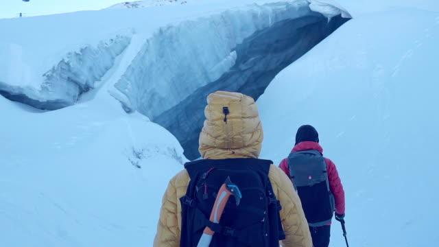 vídeos de stock e filmes b-roll de couple exploring ice cave - exploração