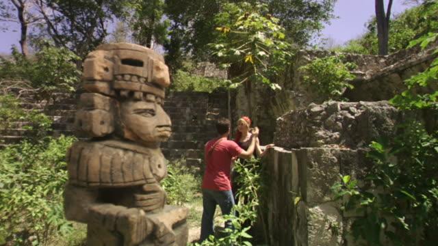 WS PAN Couple exploring Mayan ruins amid lush vegetation / Merida, Mexico