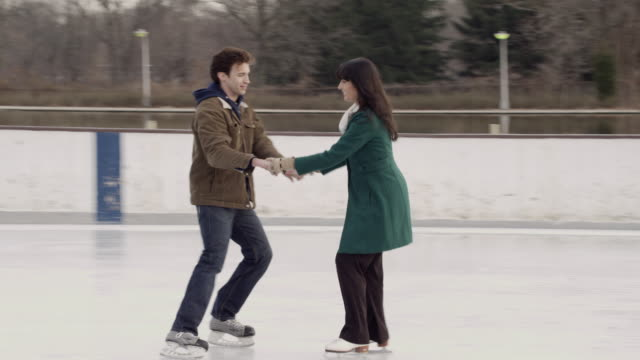 MS PAN Couple facing each other and holding hands while ice skating/ Long Island, NY