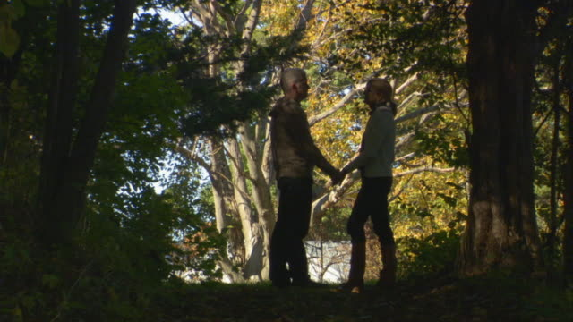 WS Couple facing each other and kissing on wooded path/ Livingston, New York