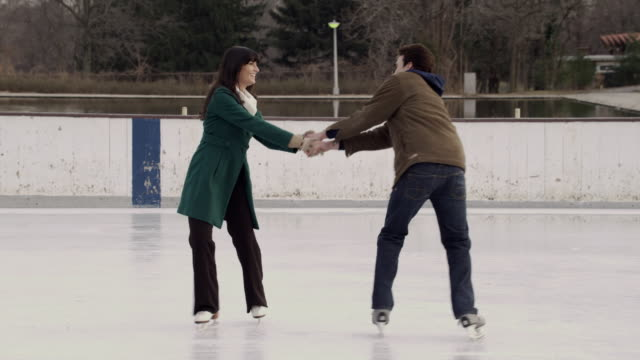 MS Couple facing each other, holding hands, and spinning on ice skates/ Long Island, NY