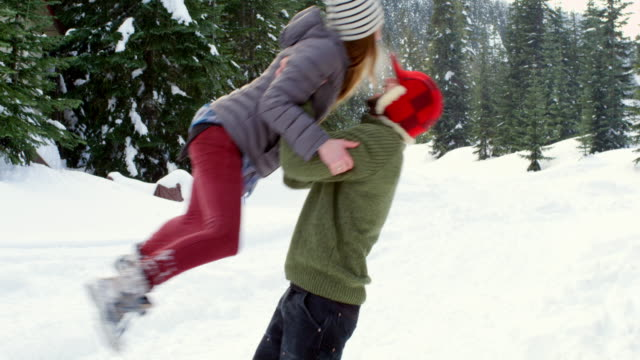 MS couple falling over into snow after woman jumps into boyfriends arms.